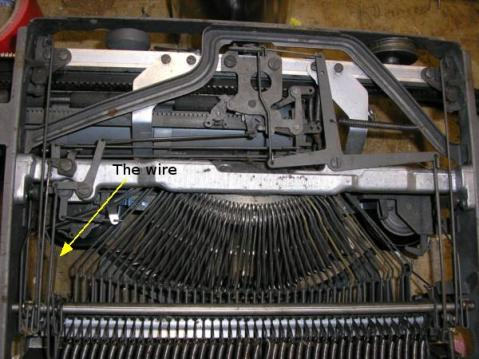Photo of the underside of the typewriter, with the wire arrowed.