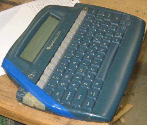 photo showing the stick taped over the top-left corner of the keyboard, where the power button is